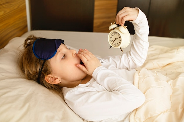 Girl hates getting up early in the morning the blonde holds the alarm clock yawning in bed covers her mouth with her hand