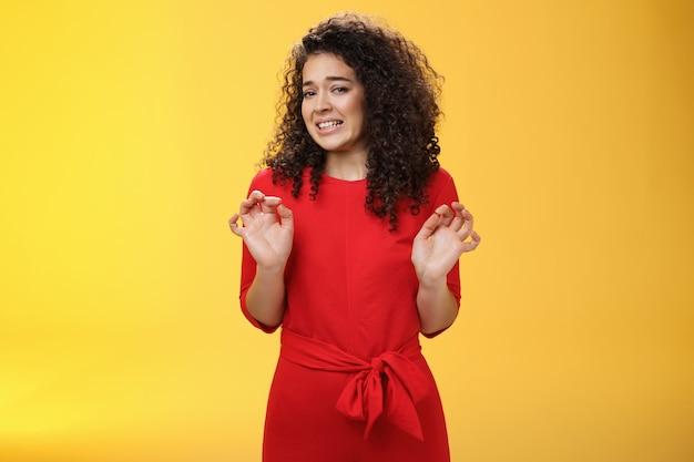 La ragazza odia lavare i piatti facendo smorfie per l'antipatia e il disgusto che vogliono vomitare dall'avversione alzando i palmi e facendo un passo indietro accigliata rifiutando un'offerta sgradevole su sfondo giallo. copia spazio