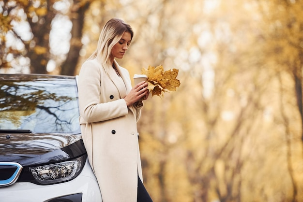 Girl have autumn trip by car. modern brand new automobile in the forest.