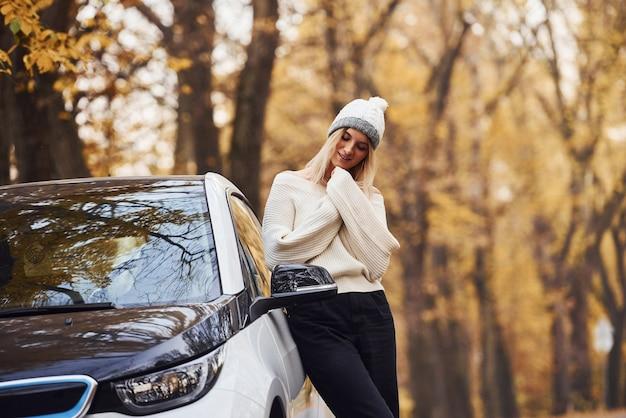 Девушка совершила осеннюю поездку на машине. современный новый автомобиль в лесу.