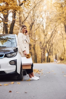 Girl have a call when stands near the car. modern brand new automobile in the forest.