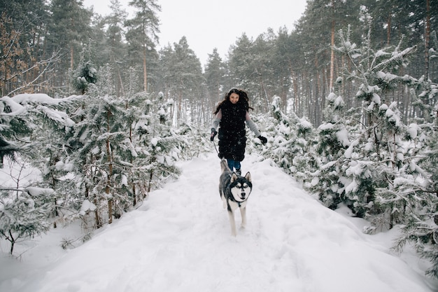 Girl have fun with her husky dog in snowy winter pine forest