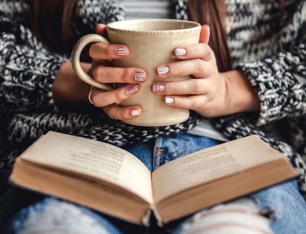 本を読んだり、勉強した後に新鮮なコーヒーのカップで休憩を持つ少女