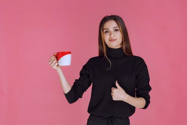 Девушка с чашкой кофе и наслаждаясь вкусом.