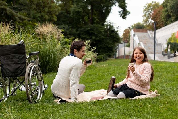 障害者の男性とピクニックをしている女の子
