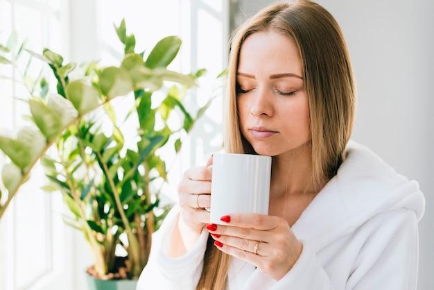 Girl having coffee at the bathroom