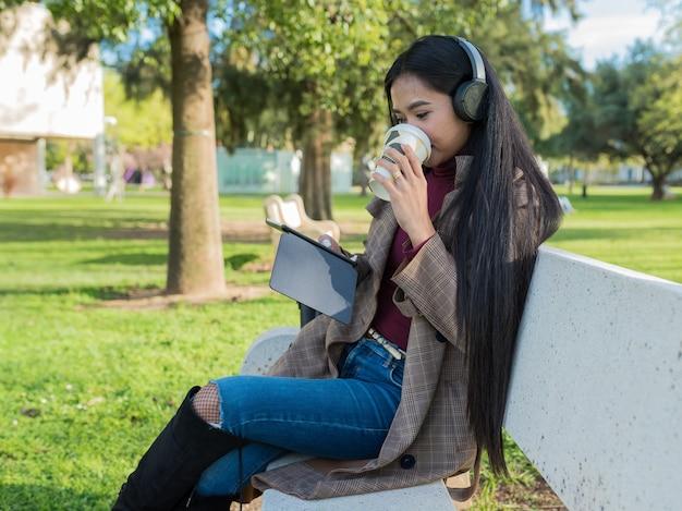 電子書籍を読んだり、公園のベンチに座って音楽を聴きながらコーヒーを飲んでいる女の子