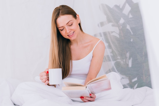 Girl having coffee with a book on the bed