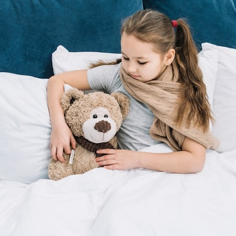 Girl having fever holding thermometer in teddy bear's hand checking the temperature