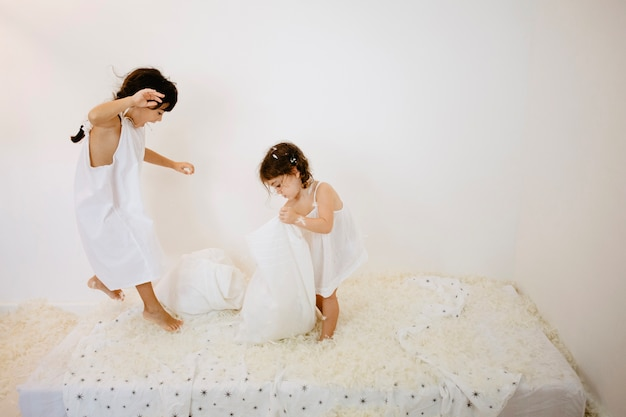 Girl having fun on mattress with sister