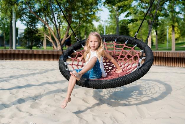 外の遊び場で大きなスイングを楽しんでいる女の子