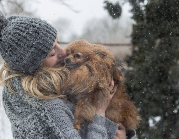 Girl having fun outside in snow with her dog yorkshire terrier.
