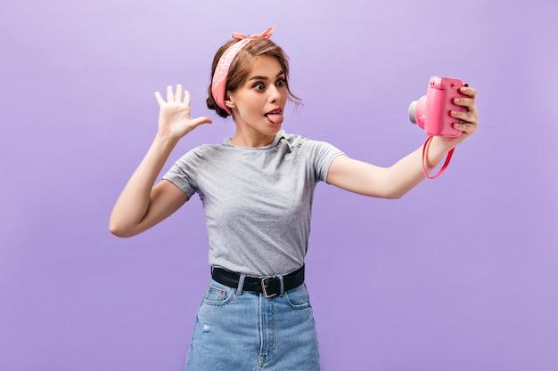Ragazza divertendosi, prende selfie su sfondo viola. giovane donna divertente di buon umore in camicia grigia e gonna di jeans su sfondo viola.