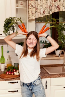Girl having fun with carrots in the kitchen