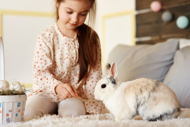 Girl having fun with rabbit on the bed