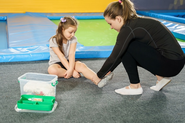 Girl having pain in ankle and getting help after jumping on trampoline
