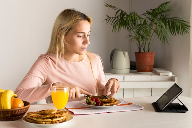 Girl having waffles watching tablet