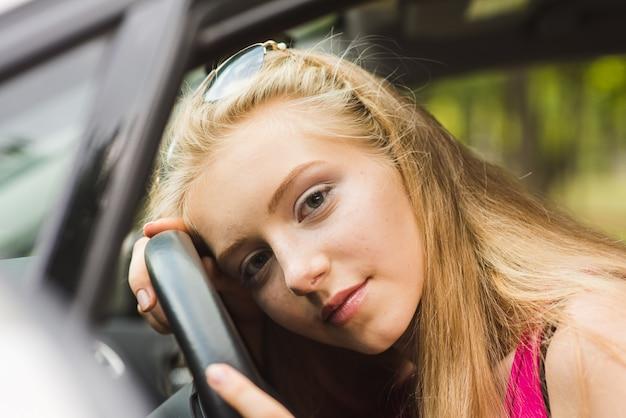 Girl head on steering wheel
