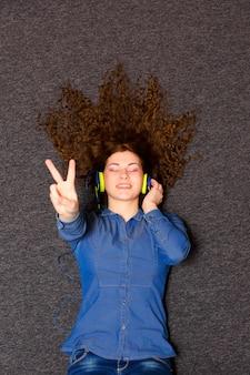 Girl in headphones enjoying music while lying on a carpet