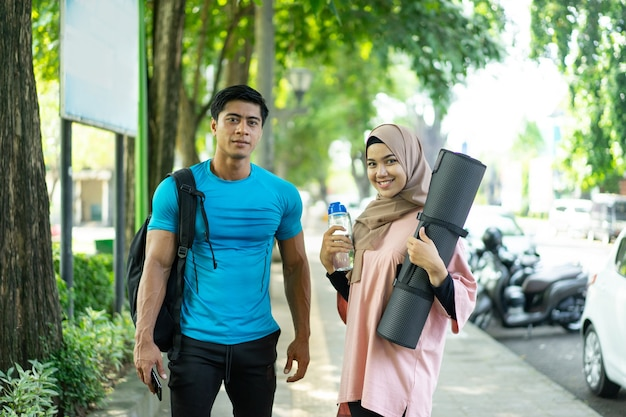 A girl in a headscarf brings a mattress and a water bottle and a man carrying a backpack smiles as he prepares for outdoor sports in the park