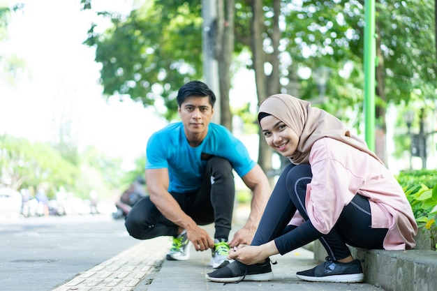 A girl in a headscarf and a man smile as they prepare to fix their shoelaces before jogging in the park