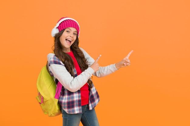 Гарнитура для девочек с рюкзаком, представляющим продукт. обратно в школу. концепция аудиокниги. онлайн-курсы. маленькая девочка слушает музыку. хорошего праздника. детский повседневный стиль. современное обучение онлайн. копировать пространство.