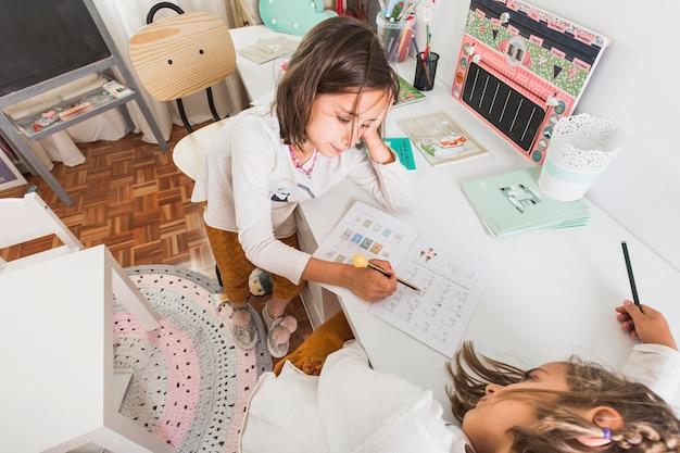 Девочка, помогая скучающей сестре с домашней работой