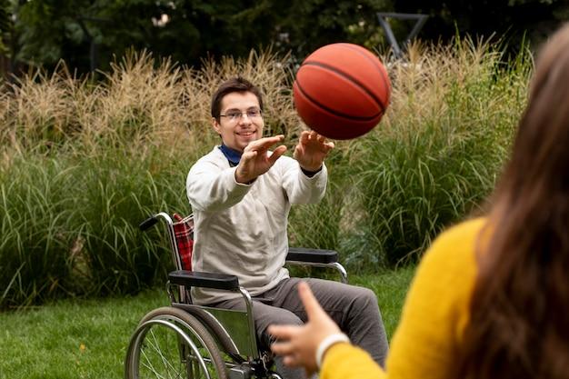 障害者の男性がバスケットボールをするのを手伝っている女の子