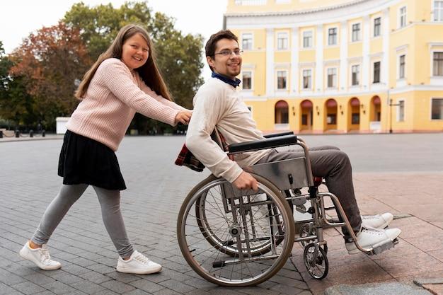 市内を旅行する障害者の男性を助ける女の子
