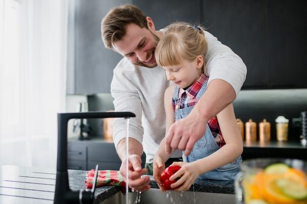 야채를 씻어 아버지를 돕는 소녀
