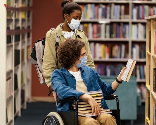 Девушка помогает своему коллеге в инвалидной коляске выбирать книги в библиотеке