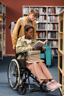 Girl helping her colleague in wheelchair choose a book for a project