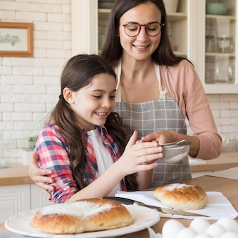Girl helping mom to cook