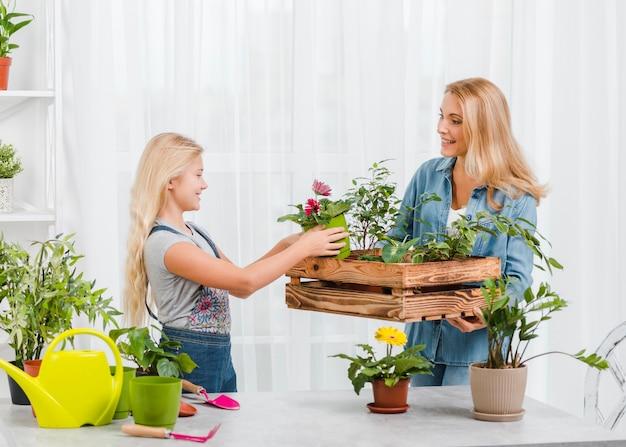Mamma d'aiuto della ragazza per prendersi cura dei fiori