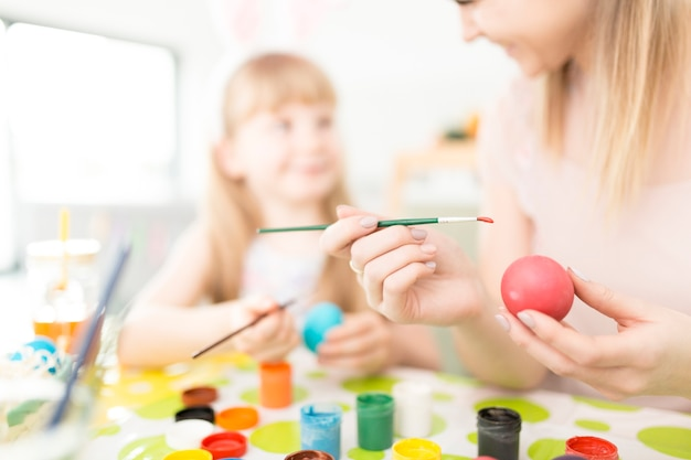 계란을 페인트 어머니를 돕는 소녀
