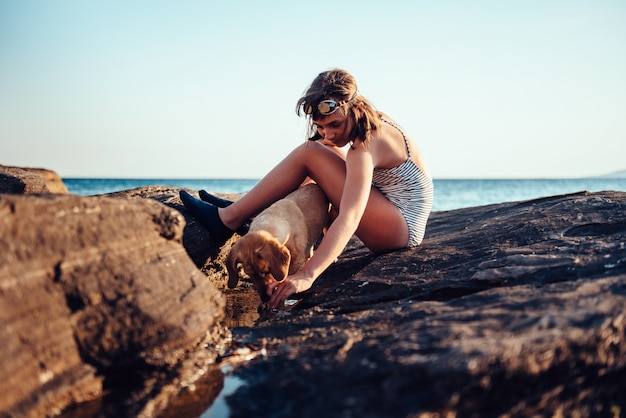 Girl and her dog exploring rocky beach