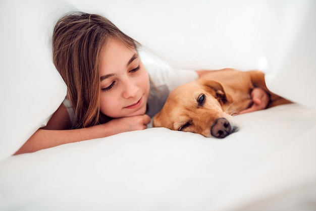 Girl and her dog lying in bed under blanket