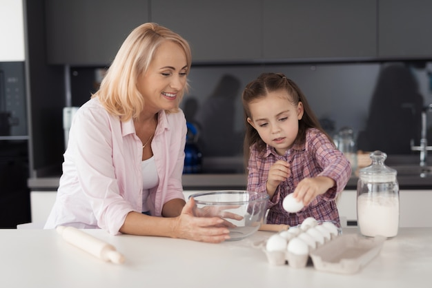 Girl and her grandmother in kitchen and preparing pastries.