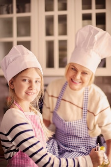 Girl and her grandmother wearing chefs hat