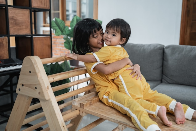 Girl and her little sister hug while playing together sitting on the pikler triangle