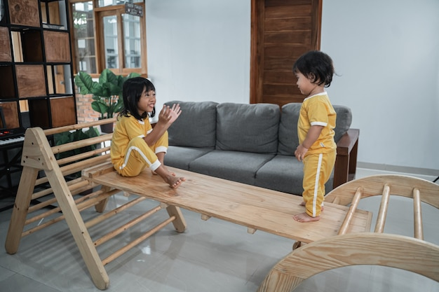 Girl and her little sister sit on the board while playing together in the pikler triangle toy
