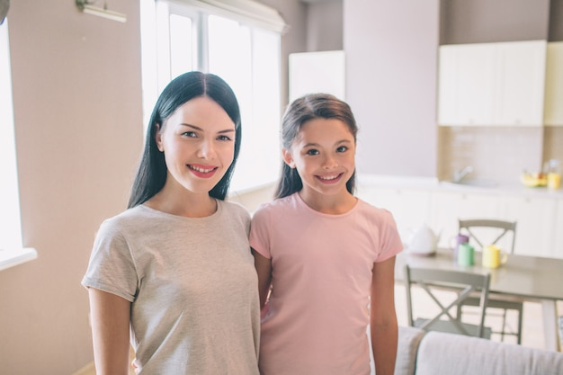 Girl and her mom are standing in kitchen and posing on camera. they smile. nice ladies are hugging each other.