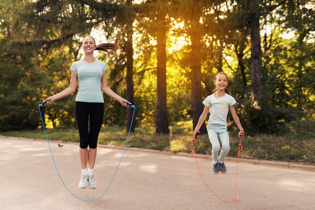 Girl and her mother jumping rope on the path in the park