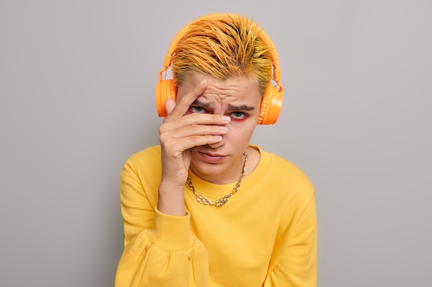 Girl hides face looks through fingers with disappointed expression has short dyed yellow hair dressed in casual jumper on grey
