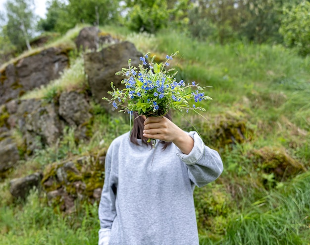 The girl hides her face behind a bouquet of fresh flowers collected in the forest