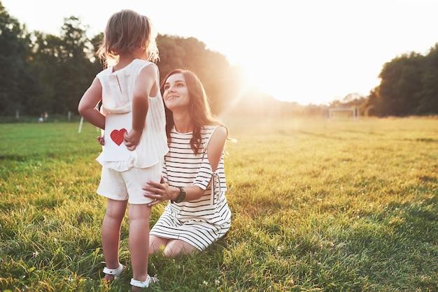 소녀는 웃는 앉아있는 어머니의 뒷면에 붉은 마음으로 책을 숨 깁니다.