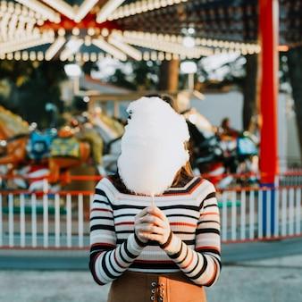 Girl hiding behind cotton candy