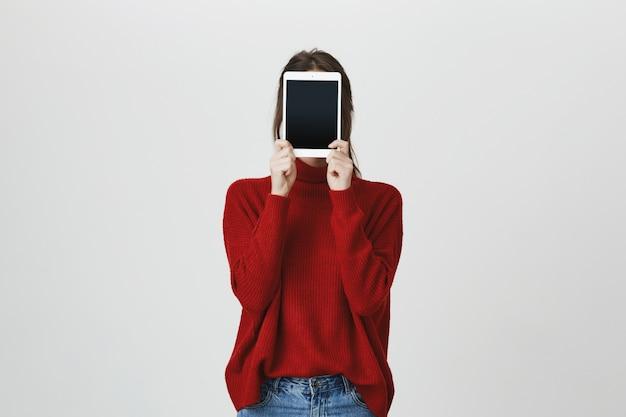 デジタルタブレットの後ろに顔を隠す女の子、ディスプレイを表示