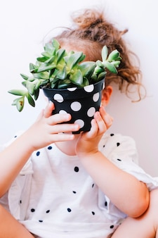 Girl hiding face behind potted plant