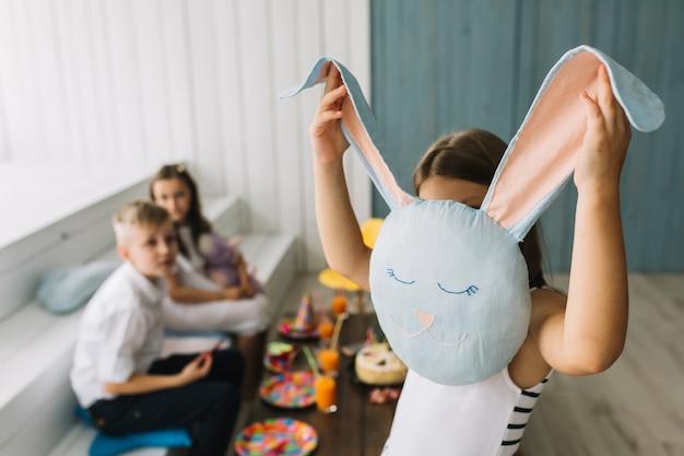 Girl hiding face behind rabbitcushion